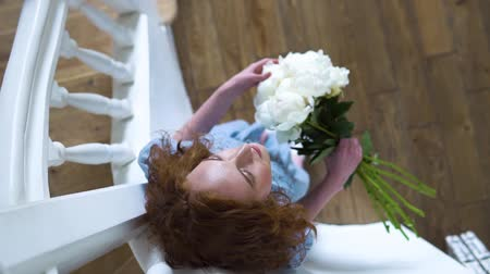 piwonie : portrait of beautiful red haired girl with big bush of white peonies