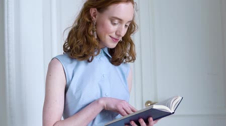 cor de malva : Young redhead girl holding and reading a book in white room