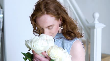 Close up portrait of beautiful red haired girl sniffs a big bush of white peonies Vídeos