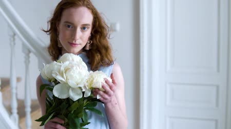 Close up portrait of beautiful red haired girl sniffs a big bush of white peonies Dostupné videozáznamy