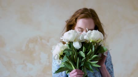 Close up portrait of beautiful red haired girl sniffs a big bush of white peonies Stock Footage