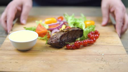 roston sült : grilled beef BBQ steak Striploin, vegetable salad and sauce on cutting Board close-up. Stock mozgókép