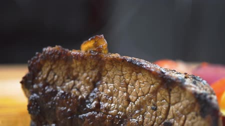 placa de corte : hot grilled beef BBQ steak Striploin, vegetable salad and sauce on cutting Board close-up Stock Footage