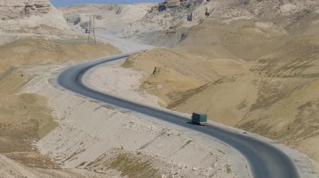 işaretler : One truck slowly climbs into the groove on a sunny road in the middle of the hills Stok Video