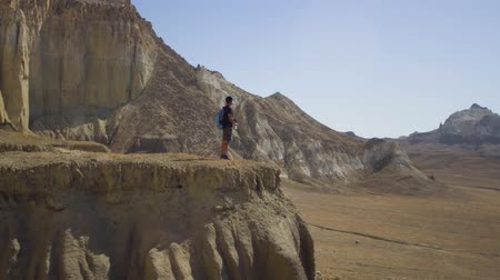 生存 : A young traveler stands on the edge of a cliff and drinks water