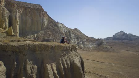 harcerz : A young traveler sits on the edge of a cliff and drinks water