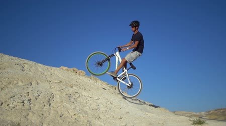 kask : A young man on a bicycle rides from a mountain and jumps on a hillock. Slow motion