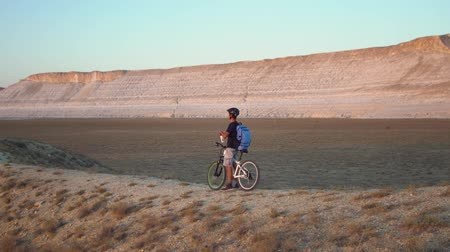 alt : A young man rides a bicycle on a background of a landscape with mountains, stops, drinks water and rides on Filmati Stock