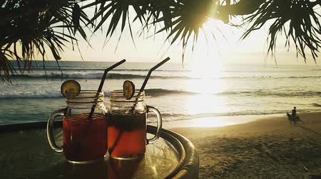 artigos de vidro : Two iced tea cocktails on table on background of palm trees at sunset Vídeos