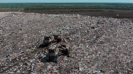 buldózer : two bulldozer working on mountain of garbage in landfill