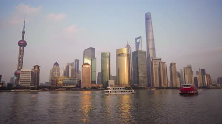 pudong : Beautiful cityscape with glass skyscrapers standing along the Huangpu River against the backdrop of the setting sun. The river is sailed by pleasure boats