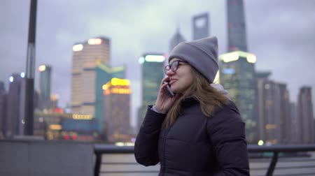 bund : a young girl in a black jacket and hat leisurely strolls while talking on the phone