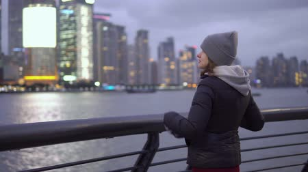 bund : a young girl in a black jacket and hat looks at the sights of Shanghai on the waterfront of the Vaitan