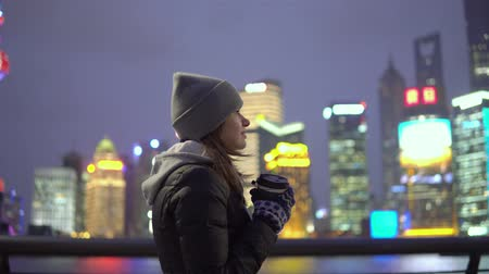 bund : a young girl in a black jacket and hat walks around the beautiful Shanghai with coffee in her hands