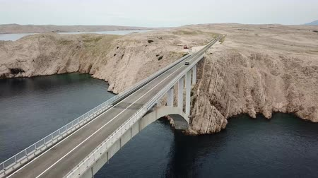 denteado : Aerial view of the bridge of the island of Pag, Croatia, road. Cliff overlooking the sea. Cars crossing the bridge seen from above