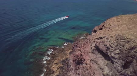 denteado : Aerial view of the jagged shores and beaches of Lanzarote, Spain, Canary. Red dinghy navigates at full speed. Roads and dirt paths. Walking routes to explore the island.