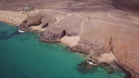 vulkán : Aerial view of the jagged shores and beaches of Lanzarote, Spain, Canary. Roads and dirt paths. Walking routes to explore the island. Bathers on the beach. Atlantic Ocean. Papagayo