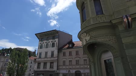 pré histórico : Central streets of the city of Ljubljana the capital and largest city of Slovenia. 06262018. People strolling in the pedestrian area of the city. Churches and castle on the hill. Slovenia flag Vídeos