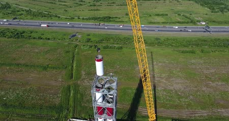 Chimney pipe construction, the crane lifts the pipe segment. Aerial shot