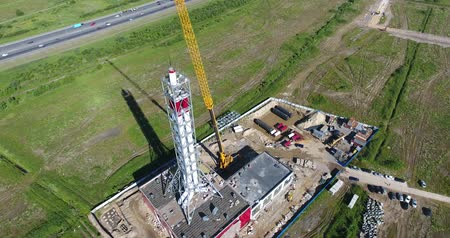 Chimney pipe construction aerial, the crane lifts the pipe segment flying around