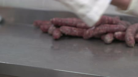 Worker packages sausages in a plastic packaging