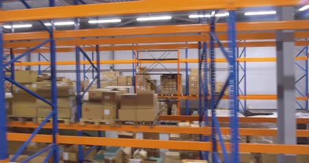inventario : Camera moves down between warehouse racks Filmati Stock