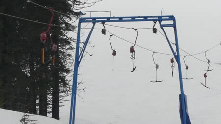 fogged : Empty surface lift - cable transport in ski resort. T-bar system.