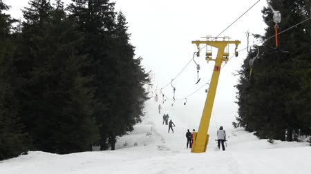 fogged : Surface lift - cable transport in ski resort. T-bar system in foggy weather. The action in real time.