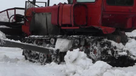 snowcat : The red caterpillar tractor removes snow from the road. The action at winter season in mountains.
