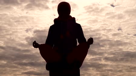 karma yoga : Silhouette of a girl sitting in the Lotus position. The action in real time. Stock Footage
