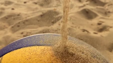 talaj : The frame in slow motion close up. Sand falls on the volleyball ball.