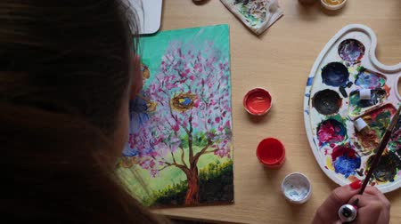 image house : In art school girl in class draws paints a picture. She uses acrylic paint.