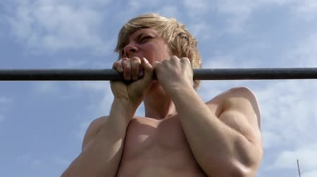lift ups : a Young Blonde Guy Pulled on the Bar. the Action in Real Time. Stock Footage