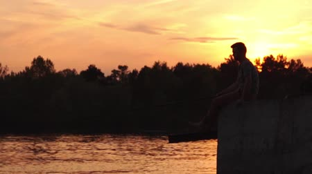 tyč : the Fisherman Sits on the Pier and Fishing. Sunset. the Action in Real Time. Dostupné videozáznamy