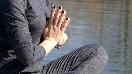 dua eden : Girl Praying With Folded Hands in Front of Chest. the Action Near Water.