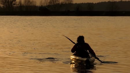 kayak : Beautiful action at sunset, the man sail on canoe in the lake.