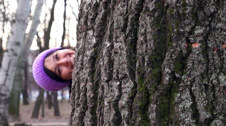 скрывать : The girl in purple hat in the woods playing hide and seek. Winter.