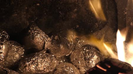 folyo : Potatoes wrapped in foil baked in the embers in the fireplace. Stok Video