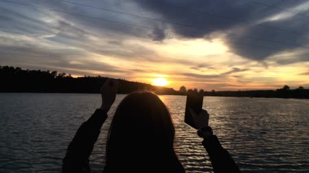 derűs : Gril rise her hands up at sunset near lake. In hands she holding smart phone. Stock mozgókép