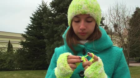 knitted gloves : The girl in green gloves is knitting a sitting on the bench in the Park. Stock Footage