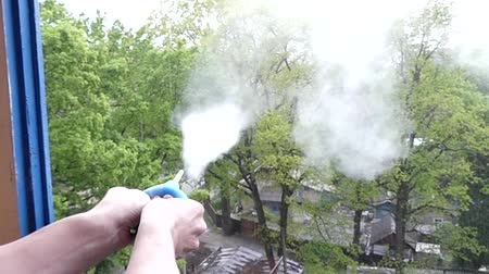 clyster : Focus: the Hand Presses the Enema and it Emits Smoke From Talc. the Action in Slow Motion.