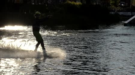 kablo : the Wakeboarder Rides on the Water in Slow Motion. Beautiful Action at Sunset.
