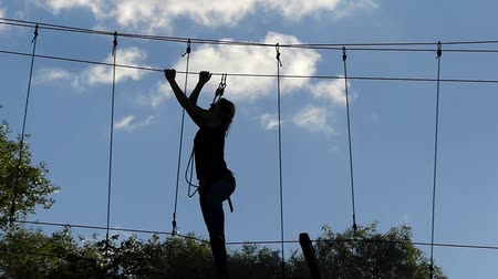 aventura : Girl on High Altitude Goes Through the Ropes. Entertainment in the Rope Park. the Action in Real Time.