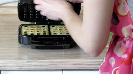 вафельный : Girl Preparing Belgian Waffles in a Special Waffle Iron.