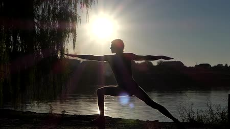 manges : Silhouette of the Man Standing on Yoga Pose Warrior. Sunset on the Lake. Beautiful Action. Stock Footage