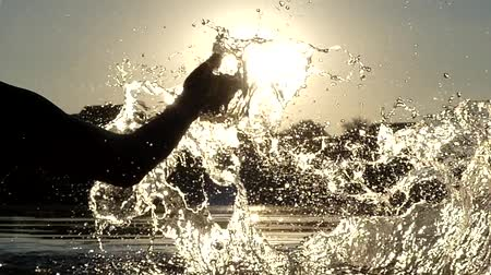 salpico : Womans Hand Make Splash in the Water in Slow Motion During Sunset. Beautiful Action Close Up.