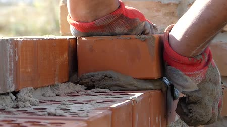 manges : Hands of the Builder Put a Cement Mortar. Hand Makes the Masonry of Brick. the Action in Real Time. Close up Shot. Stock Footage