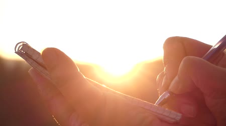 notebooklar : the Girls Hand Making Notes in a Notebook at Sunset in Rays of the Sun. Beautiful Action. Stok Video