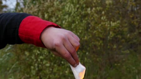 gimmick : Man`s Hand Uses a Lighter And Ignites White Paper on a Lawn in Slo-Mo