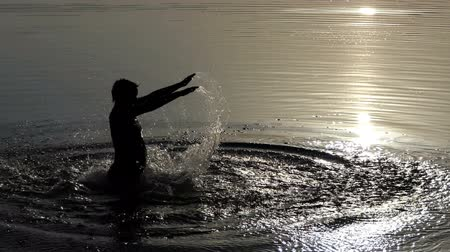 confecção : A woman jumps in a lake and makes a fountain with hands in slo-mo